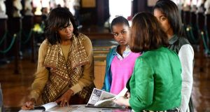 US First Lady Michelle Obama with her daughters Sasha and Malia: having visited Trinity College's Long Room to view the Book of Kells yesterday, they go to see Glendalough today.  Photograph: Cyril Byrne
