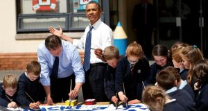 US president Barack Obama reacts as the sun comes out as he works alongside Britain's prime minister David Cameron and students on a school project about the G8 summit during a visit to the Enniskillen Integrated Primary School yesterday. Photograph: Reuters