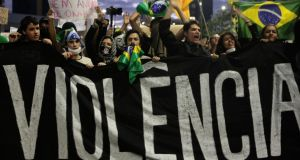 Demonstrators shout anti-government slogans behind a banner, which reads as 'violence', during a protest in Sao Paulo yesterday. Photograph: Reuters