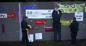 Police remove anti-G8 signs from the security fence at the G8 summit venue at Lough Erne. Photograph: Peter Macdiarmid/Getty Images