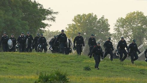 Police with riot shields react as protesters breach the Lough Erne cordon. Photograph: Niall Carson/PA Wire