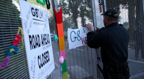 A police officer removes anti-G8 signs from the security fence at the G8 summit venue. Photograph: Peter Macdiarmid/Getty Images