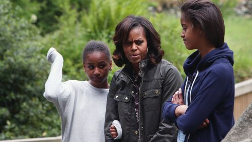 First Lady Michelle Obama and her two daughters Malia Ann (right) and Sasha fight off an unwelcome attack of midges. Photograph: Julien Behal/PA Wire