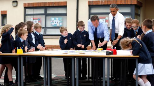 President Barack Obama and British prime minister David Cameron help students with a school project about the G8 summit. Photograph: Matt Dunham/WPA Pool/Getty Images