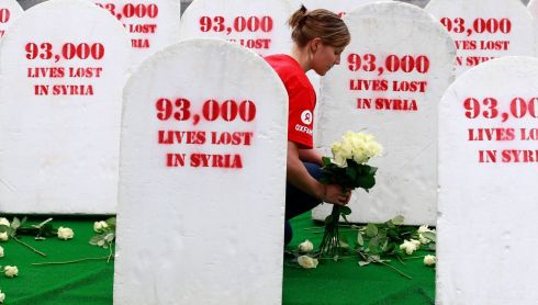 A member of Oxfam lays flowers today at mocked up gravestones in memory of lives lost in Syria in front of Belfast City Hall, ahead of Barack Obama's visit to the city.  Photograph: Cathal McNaughton/Reuters
