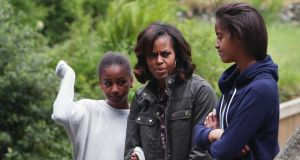 US first lady Michelle Obama and her two daughters Sasha and Malia  fight off an unwelcome attack of midges at Glendalough. Photograph: Julien Behal/PA Wire