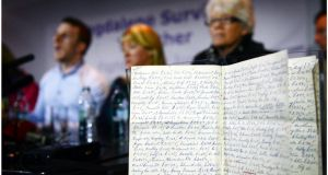 Members of Magdalene Survivors Together  react to the publication of the Magdalene Report; in the foreground is an old Magdalene Laundry ledger. Photograph: Bryan O'Brien
