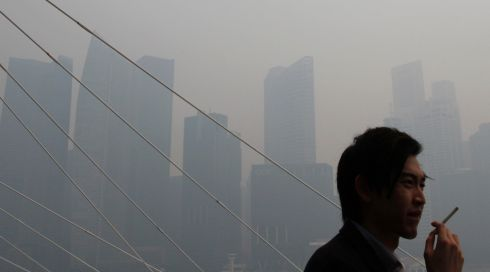 Just can't get enough: a man smokes a cigarette in front of the hazy skyline of Singapore. Photograph: Edgar Su/Reuters