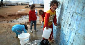 A Syrian child gathers water in the Za'atari refugee camp in Mafraq, Jordan. Record numbers of refugees are fleeing the violence and bombings in Syria to cross the borders to safety in northern Jordan and overwhelming the camp. Photograph: Getty Images