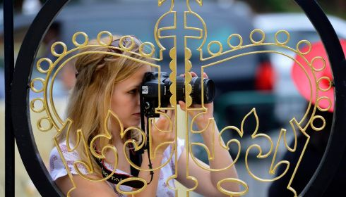 A woman takes photographs through the fence of the royal enclosure on Ladies' Day. Photograph:  Toby Melville/Reuters