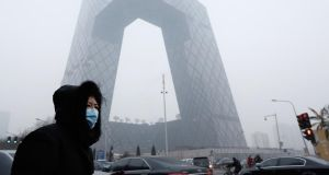 A woman wearing a mask walks past the CCTV building during severe pollution on January 23rd this year in Beijing. There is growing public anger about pollution in China. Photograph: Lintao Zhang/Getty Images