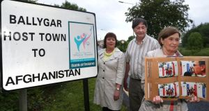 Mary O'Keeffe, who was chairperson of the Ballygar Special Olympics Host Town for the Afghan team in 2003, displaying an album of photographs from the time at the sign which still stands at the entrance to Ballygar. Included in the photograph are Geraldine Kelly who was secretary and Pat Gilmore who was public relations officer. Photograph: Joe O'Shaughnessy. 13/6/2013