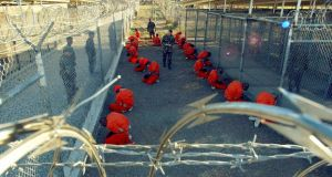 Detainees sit in a holding area watched by military police at Camp X-Ray inside naval base Guantánamo Bay, Cuba, in this January  11,  2002 file photo. Photograph: US department of defence/Reuters