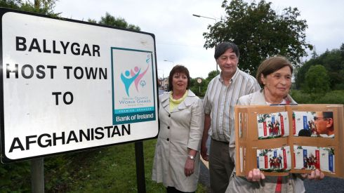 Mary O'Keeffe, who was chairperson of the Ballygar Special Olympics Host Town for the Afghan team in 2003, displaying an album of photographs from the time at the sign which still stands at the entrance to Ballygar. Included in the photograph are Geraldine Kelly who was secretary and Pat Gilmore who was public relations officer.  Photograph: Joe O'Shaughnessy/The Irish Times