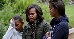 Can we go now?: Sasha and Malia Obama, with their mother, Michelle, fight off boredom and midges at Glendalough this week. Photograph: Julien Behal/PA