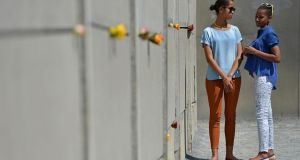Malia and Sasha Obama visit the Berlin Wall memorial  this week. Photograph:  Miriam May/Pool /Getty Images