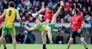 Donegal's Ryan Bradley takes a tumble after being challenged by Calum King. Photograph. Morgan Treacy/Inpho