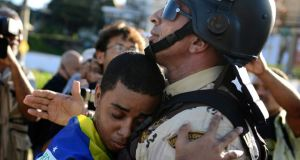 A demonstrator embraces a police commander in a gesture of peace during a protest in Salvador. Photograph: Reuters/Valter Pontes