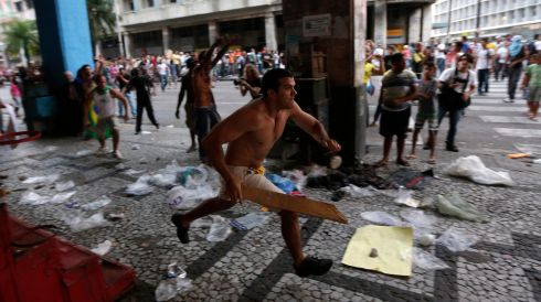 A demonstrator chases vandals in Recife City. At least one protester was killed in Sao Paulo state when a car rammed into a crowd of demonstrators, after the driver apparently became enraged about being unable to drive along a street.  Photograph: Ricardo Moraes/Reuters