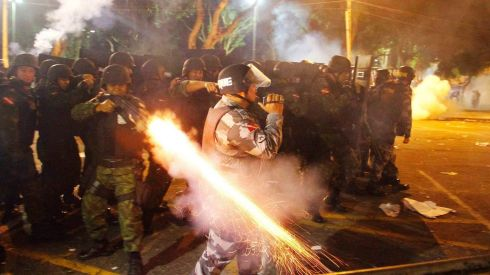 A riot policeman fires his weapon while confronting stone-throwing demonstrators during an anti-government protest in Belem. Photograph: Ney Macondes/Reuters