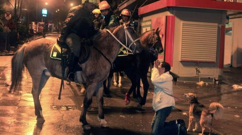 A woman kneels in front of mounted riot policemen in Porto Alegre. Photograph: Gustavo Vara/Reuters