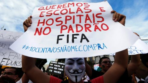 A demonstrator wearing a Guy Fawkes mask holds up a sign during a protest against the Confederations Cup and President Dilma Rousseff's government, in Recife City.  Photograph: Marcos Brindicci/Reuters