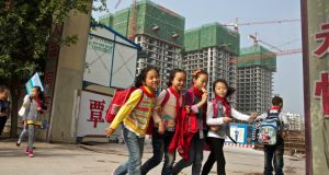 Children walk home from school to a housing project in Chongqing, the fastest growing city for dollar multi-millionaires in China between 2007 and 2012. Photograph: Justin JinNew York Times