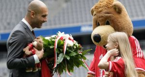 Pep Guardiola  of Bayern Munich talks to a ball girl next to club mascot 'Berni' the bear at Bayern Munich's Allianz Arena. Photograph: Michaela Rehle/Reuters