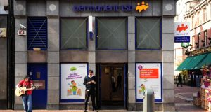 A busker stands outside a branch of the Permanent TSB on Grafton Street in Dublin. Photograph: Aidan Crawley/Getty Images