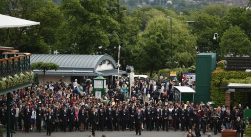 Carefully does it: Tournament stewards escort fans into the grounds of Wimbledon. Photograph: Dan Kitwood/Getty Images