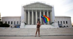 Vin Testa waves a rainbow flag in front of the US Supreme Court in Washington today after the court ruled that the Defense of Marriage Act is unconstitutional. Photograph: Christopher Gregory/The New York Times