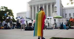 Oscar Soto wraps a rainbow flag around his shoulders while waiting for a ruling from the U.S. Supreme Court in Washington, June 26, 2013. The court ruled Wednesday that the 1996 law denying federal benefits to legally married same-sex couples is unconstitutional, in a sign of how rapidly the national debate over gay rights has shifted. (Christopher Gregory/The New York Times)