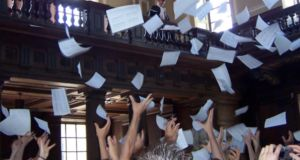 The results of the final examinations in mathematics being read out at Cambridge University. Following tradition, the class list is then tossed over the balcony, and the names of this year's Wranglers are known