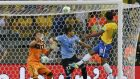 Brazil's Paulinho (right) heads  past Uruguay's Martin Caceres and goalkeeper Fernando Muslera (left) to book final berth. Photograph: Sergio Moraes/Reuters
