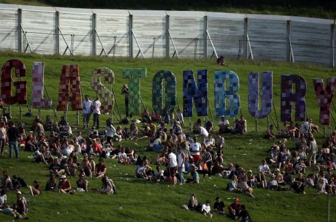 People sit in the sun below the Glastonbury sign on the first day of the event. Photograph: Matt Cardy/Getty Images.