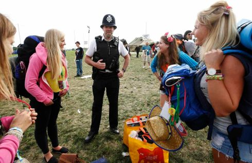 A policeman warns campers about recent thefts on site as they arrive on the second day of the festival. Photograph: Olivia Harris/Reuters