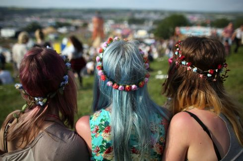 Three festival goers sit and look at the view over the fields. Photograph: Matt Cardy/Getty Images