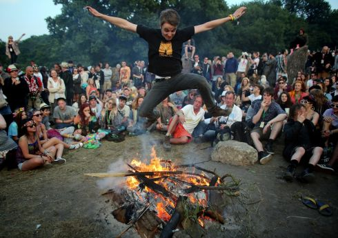 A man jumps over a fire that has been lit inside the stone circle. Photograph: Matt Cardy/Getty Images