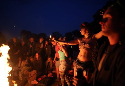People dance around a fire inside the stone circle as people gather for sunset at the Glastonbury site on the first night of the event. Photograph: Matt Cardy/Getty Images