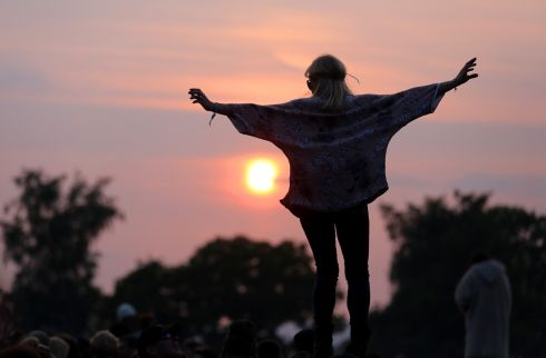 A woman stands on a rock at the stone circle as people gather for sunset on the first night of the festival at Worthy Farm. Photograph: Matt Cardy/Getty Images