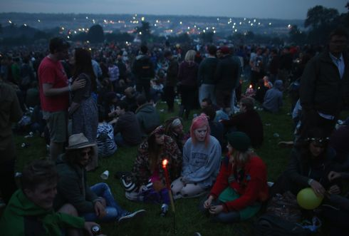 Music fans gather around a candle on the first night of the event. Photograph: Matt Cardy/Getty Images