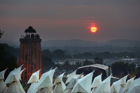 The sun begins to set over tipis at the Glastonbury Festival of Contemporary Performing Arts site at Worthy Farm, Pilton on June 26th, 2013.  Gates opened on Wednesday for one of the largest music festivals in the world and this year features headline acts Artic Monkeys, Mumford and Sons and the Rolling Stones. Tickets to the event which is now in its 43rd year sold out in minutes and that was before any of the headline acts had been confirmed.  Photograph: Matt Cardy/Getty Images