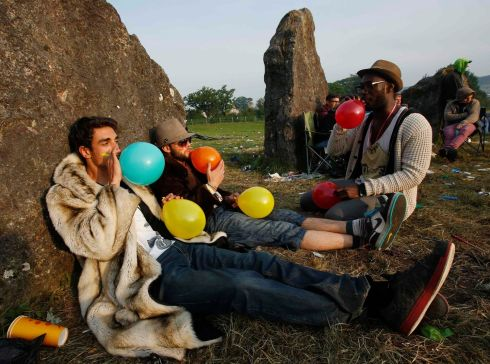 Festival goers inhale laughing gas at sunrise at the stone circle. Photograph: Olivia Harris/Reuters