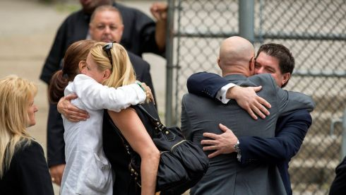 Mourners embrace outside the funeral. Phootgraph: Lucas Jackson/Reuters