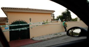 A woman looks over the wall of a house cordoned off by the Spanish civil guard, where three members of a family were found dead inside, in Mijas Costa, near Malaga southern Spain.