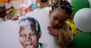 Two-year-old Precious Mali holds a picture of former South African President Nelson Mandela as well-wishers gather outside the Medi-Clinic Heart Hospital. Photograph: Dylan Martinez/Reuters