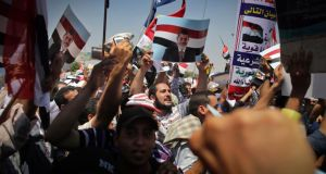 Supporters of Egyptian President Mohamed Morsi hold up posters of him and wave their national flag.