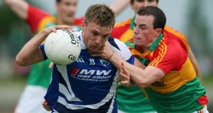 Carlow's Barry-John Molloy tackles Ross Munnelly of Laois. Photograph: Lorraine O'Sullivan/Inpho