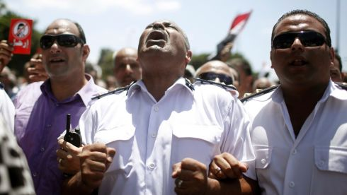 A police officer shouts 'Leave' during an anti-Morsi protest with other police officers and protesters after attending the funeral of Brigadier General Mohamed Hani. Photograph: Asmaa Waguih/Reuters