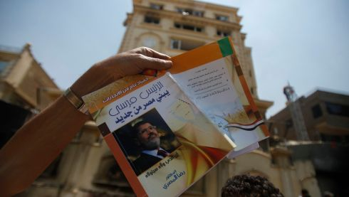 "A protester, opposing Egyptian president Mohamed Morsi, holds a book titled ""President Mursi Building a New Egypt"" in front of the headquarters of the Muslim Brotherhood in Cairo's Moqattam district. The Brotherhood said armed men who ransacked its national headquarters had crossed a red line of violence, and the movement was considering action to defend itself. Hundreds of people threw petrol bombs and rocks at the building, which caught fire as guards and Brotherhood members inside the building exchanged gunfire with attackers.  Photograph: Amr Abdallah Dalsh/Reuters"